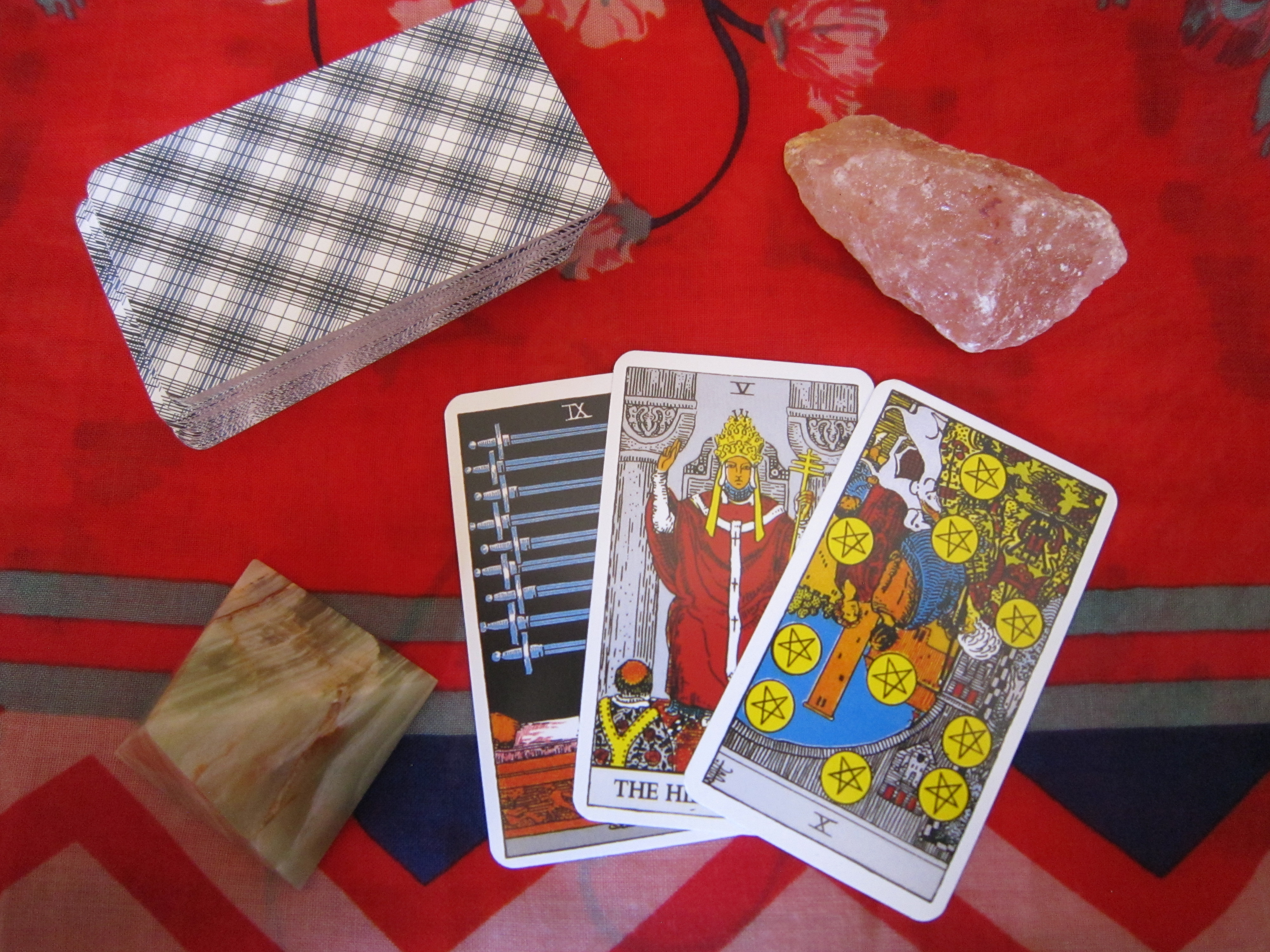Tarot card reading with 3 cards which show the 9 of swords, the heirophant, and the ten of pentacles.